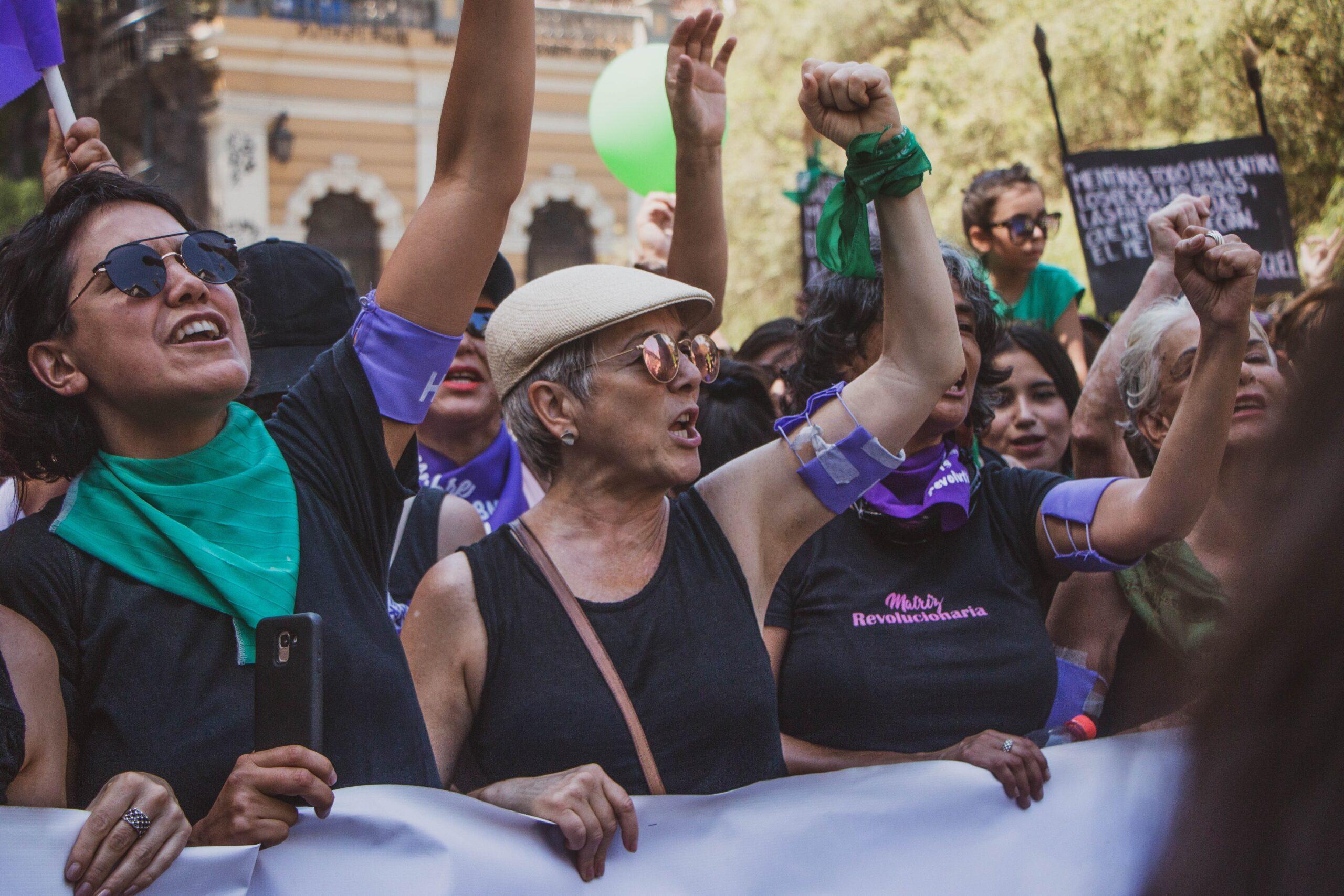 mujeres marchando por la igualdad con pañuelos verdes y morados