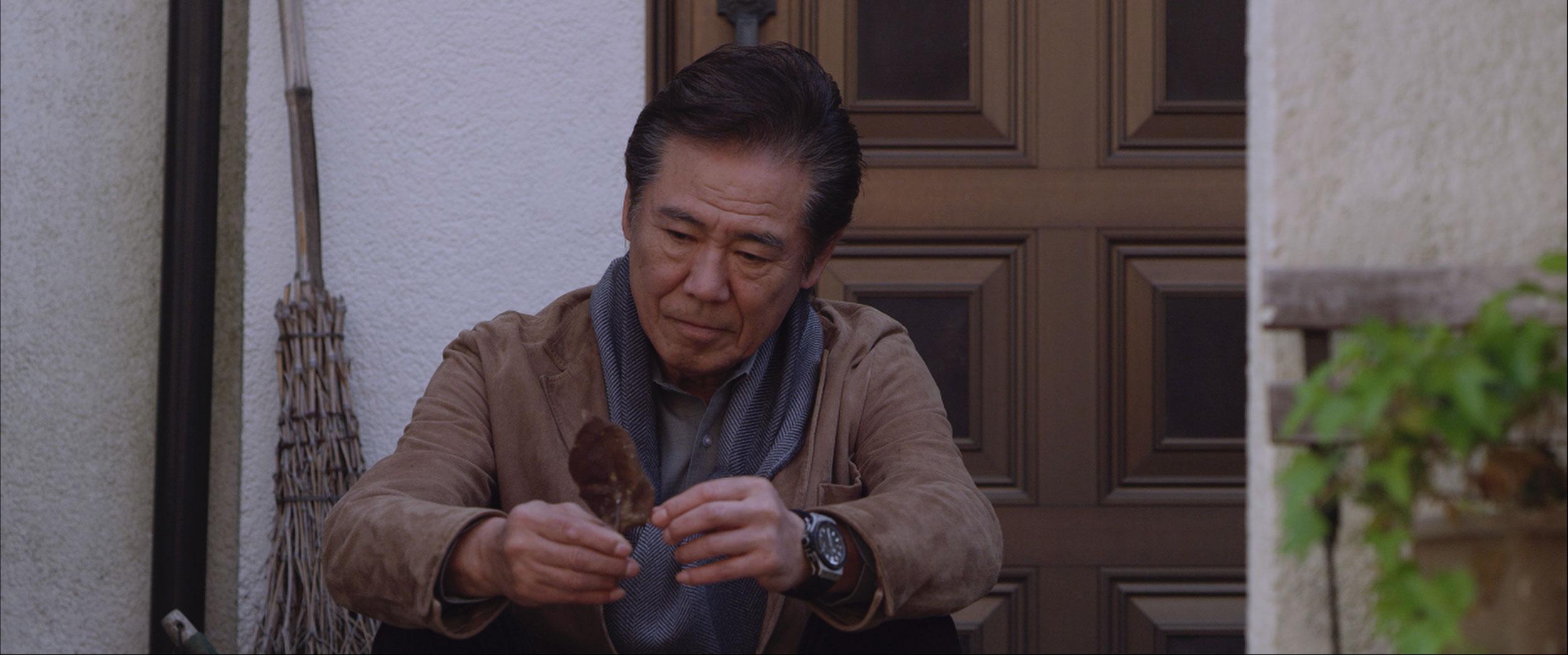 hombre japonés sentado mirando una hoja
